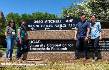 Four people stand by the UCAR building sign, which has been incorporated into the end of a large and sturdy retaining wall. 3450 Mitchell Lane. FL0 BLDG. FL3 BLDG. FL1 BLD. UCAR University Corporation for Atmospheric Research.