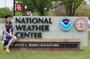 Elizabeth Leslie sits on the edge of the National Weather Center sign, wearing her graduation cap. OU, National Weather Center, NOAA, 120 David L. Boren Boulevard.