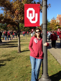 Stephanie Buway wears an OU hoodie, holding onto a lamp post, an OU banner hanging over her head. OU