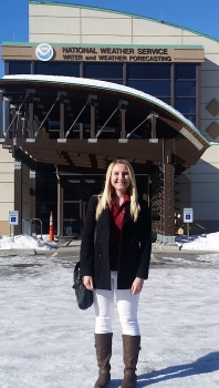 Tabitha Kloss in front of the National Weather Service Water and Weather Forecasting building in Alaska. National Weather Service Water and Weather Forecasting.