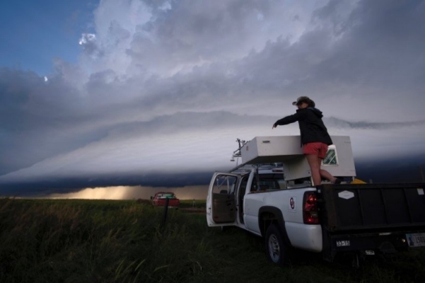OU CIMMS Researcher Elizabeth Smith preparing the LiDAR system for operation on the outskirts of a storm. (Photo by Mike Coniglio/NOAA NSSL)