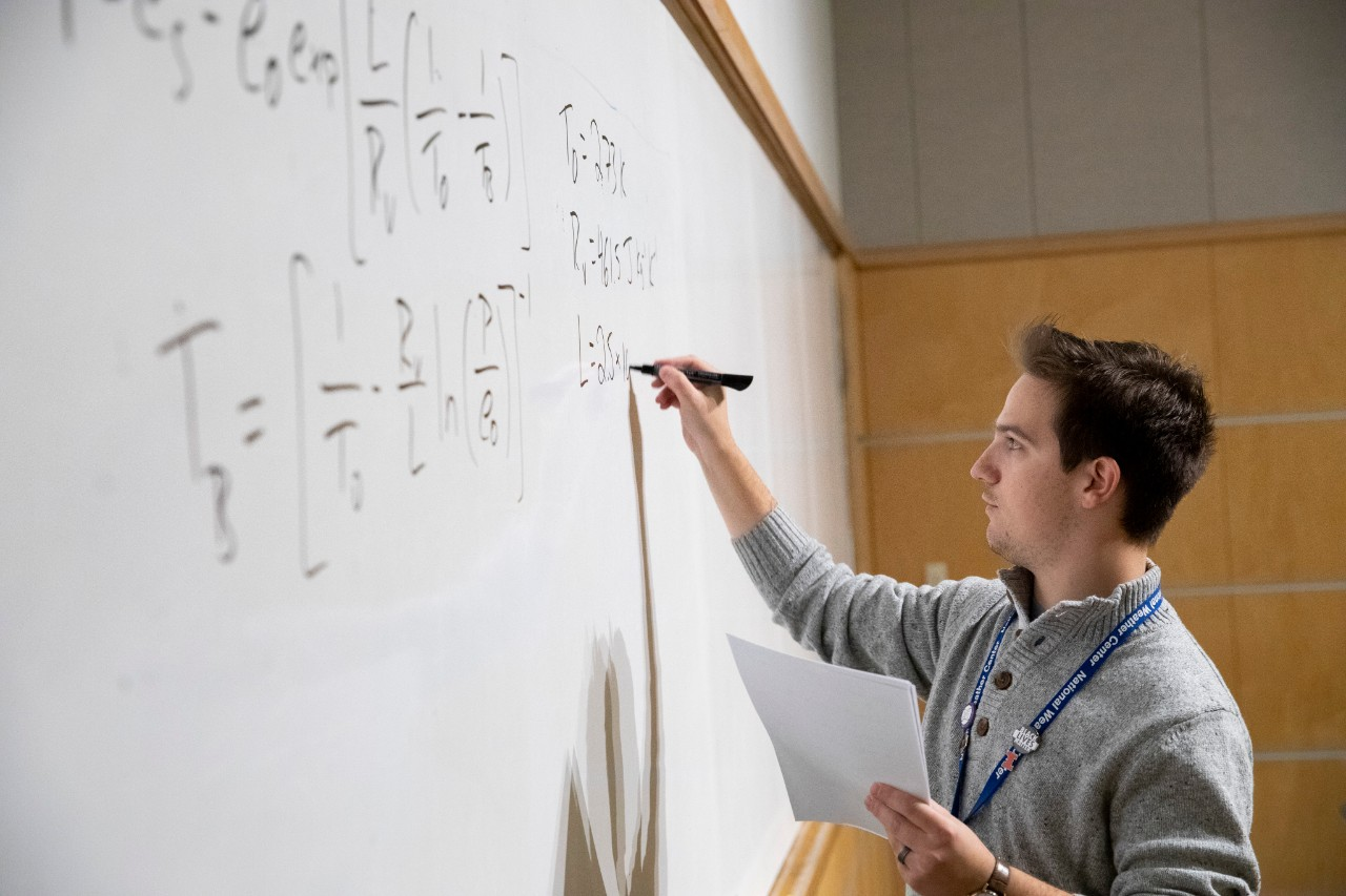 An instructor  displays a calculus equation related to thermodynamics on a whiteboard in a classroom in the National Weather Center.