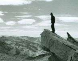 Photograph of Ken Taylor standing on the edge of a rock outcropping