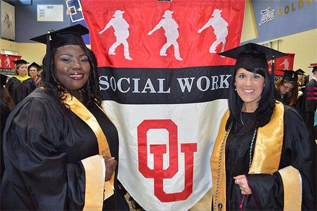 Image of students at Social Work graduation with flag