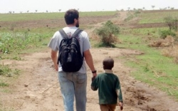 Water Center Student walks with boy in Uganda