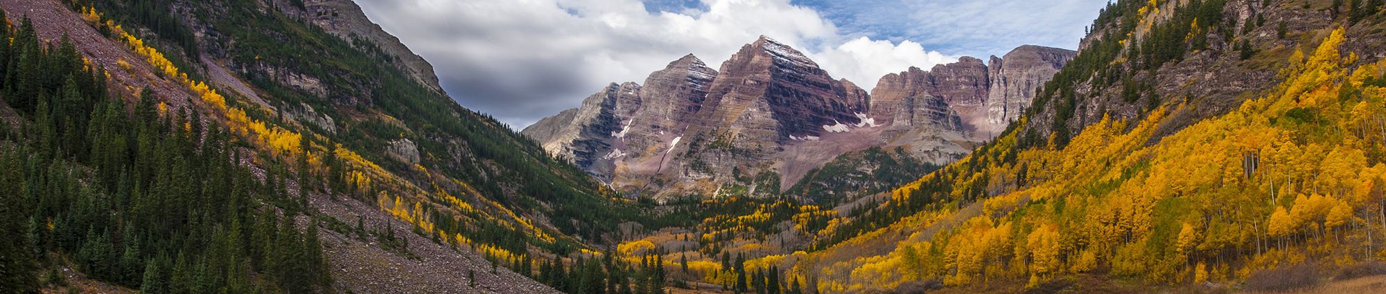 A magnificent view of Maroon Bells in Colorado – two peaks in the Elk Mountains, each over 14,000' feet high.  The photo shows the peaks and their crystal-clear reflection in Maroon Lake below.  Golden Aspens line the lake and are also reflected, as are several friendly clouds in the sky above.