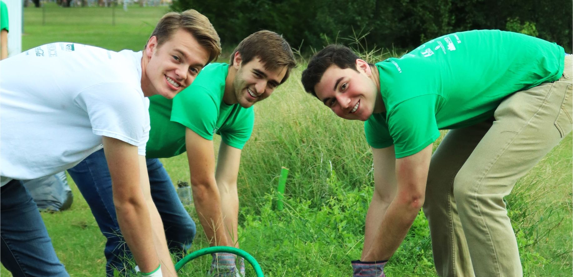 Three guys posing as they pull weeds