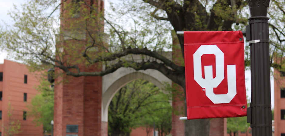 OU flag on a light pole with campus archway, Lindsey Street, and Cate Centers One and Two in background