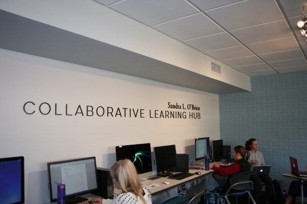 Wall sign and computer workstations at the Sandra L. O'Brien Collaborative Learning Hub