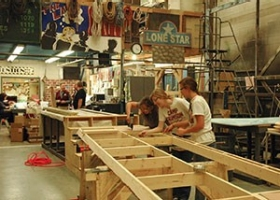 students lay out wood panels for set design