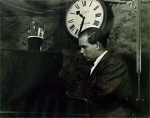 black and white image, man playing piano, pitcher sitting on piano, clock behind him