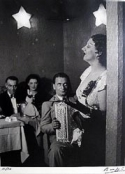 black and white image, woman singing inside Cabaret, accordian player gazing up at her, couple sitting at table in background