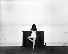 black and white image, nude woman standing with her back to the camera, left leg bent to create a 4 shape with her legs