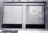 black and white image, two large windows, view from outside of building, curtains closed, can't see inside windows