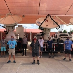 OU and NOAA personnel stand in front of radar trucks at the National Weather Center.