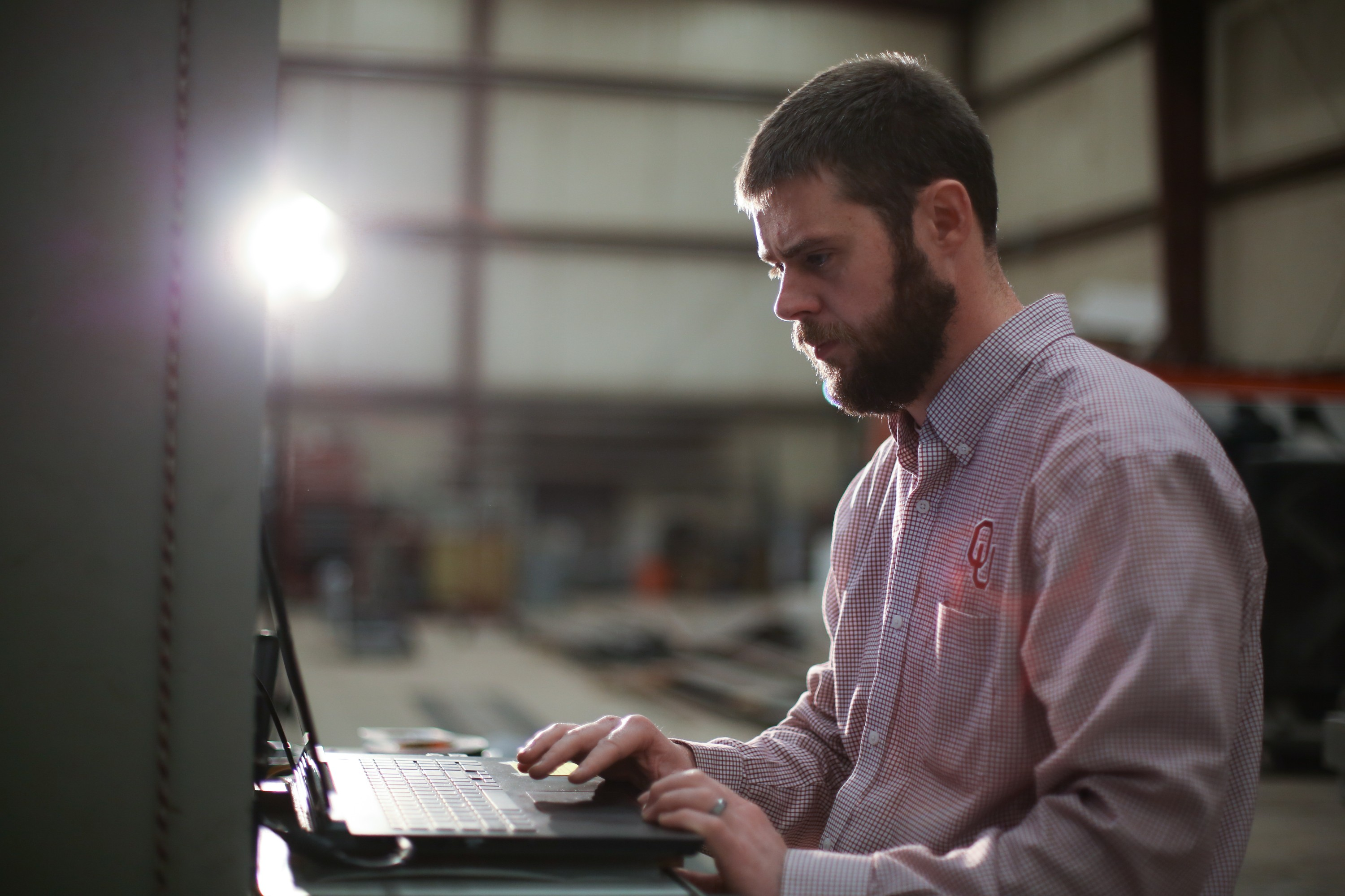 An OU Engineer at Fears Lab works on his laptop.