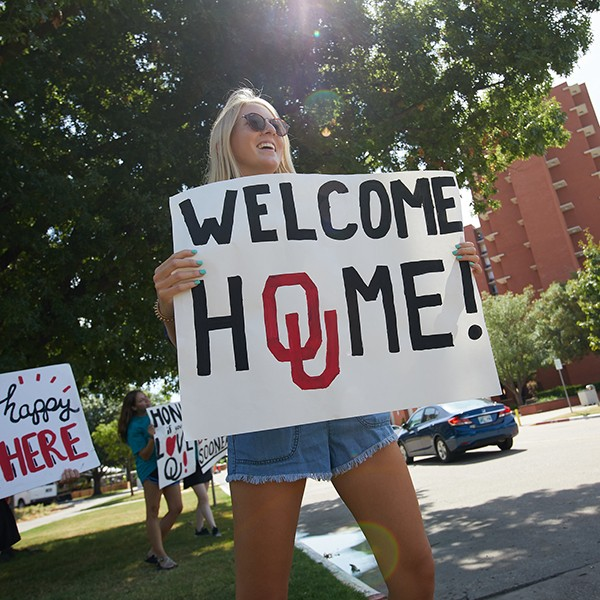 student holds up welcome sign