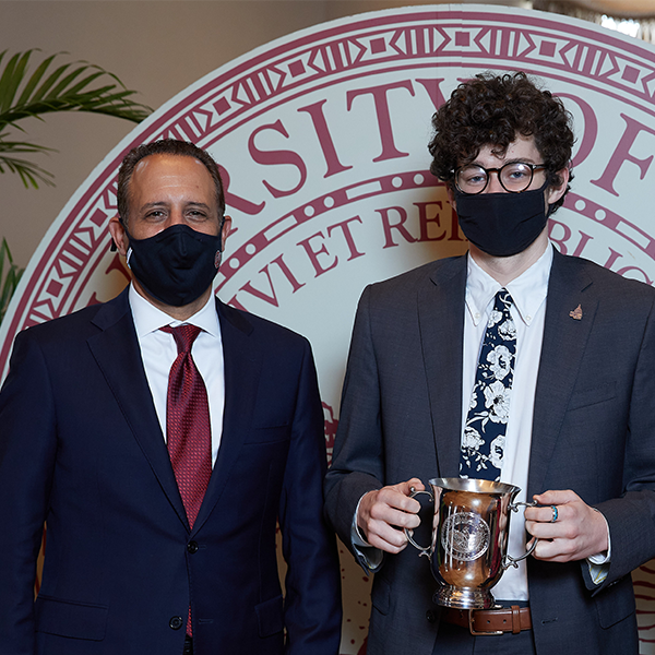 Carson Ball poses with President Harroz, both wearing COVID masks